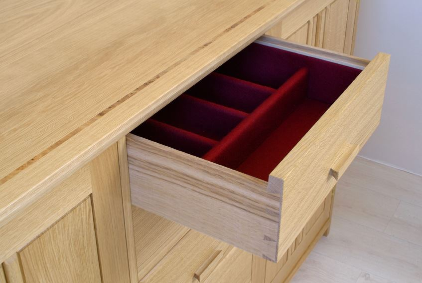 wooden drawer open with red felt lining